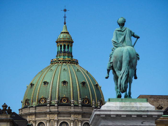 Statue in front of copenhagen cathedral against clear blue sky