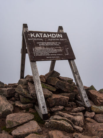 A wooden sign on the summit of Katahdin in Baxter State Park, Maine, marking the northern terminus of the Appalachian Trail. Rock Rock - Object Sign Information Nature Outdoors Wood - Material No People Appalachian Mountains Appalachian Trail Baxter State Park Katahdin Mountain Mount Katahdin Hiking Trail Trail Sign Stone Overcast Cloud - Sky Mountain Peak Information Sign Hike Western Script Text
