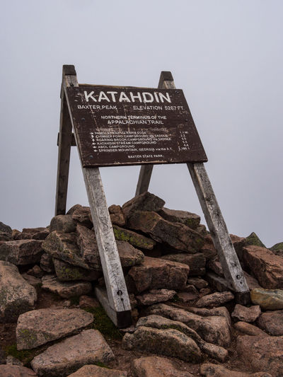Low angle view of text on rock against clear sky