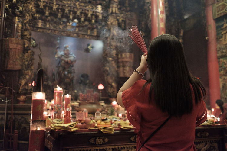Benoa, Bali, Indonesia - January 28, 2017 : People praying and wishing a happy chinese new year on vihara satya dharma. Adult Architecture Built Structure Casual Clothing Focus On Foreground Food And Drink Glass Hair Hairstyle Holding Indoors  Leisure Activity Lifestyles Long Hair One Person Real People Rear View Three Quarter Length Waist Up Women