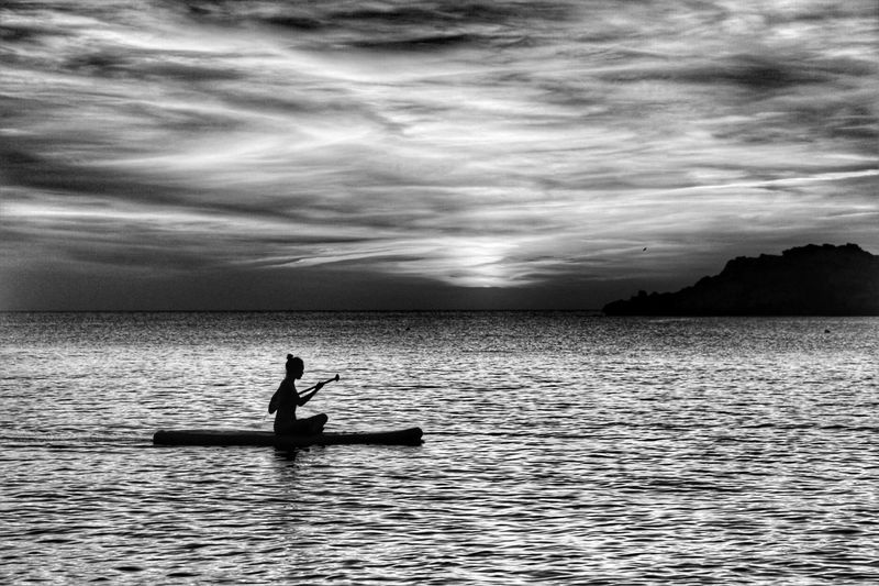 Silhouette man sitting on boat in sea against sky