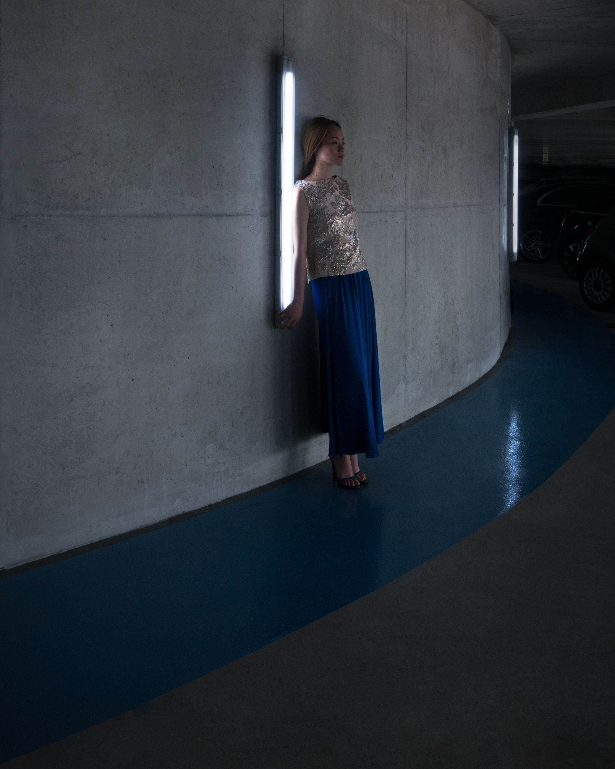 full length, one person, indoors, wall - building feature, fashion, women, standing, dress, real people, lifestyles, architecture, young adult, adult, clothing, young women, leisure activity, blue, built structure, contemplation, hairstyle, beautiful woman