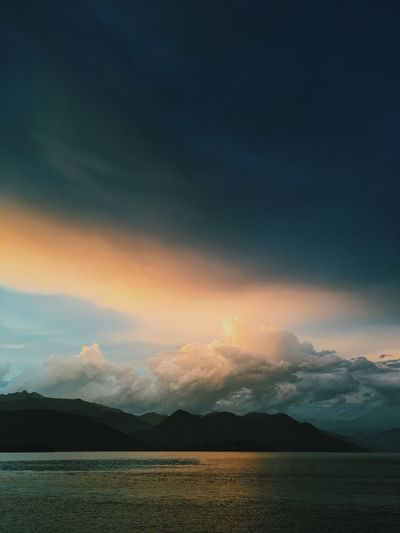 Clouds gather above the lake, Italy. Clouds Gathering Dark Clouds Fluffy Clouds Gold Light Golden Hour Horizon Over Water Lake Lake View Mountains Sky Storm Storm Clouds