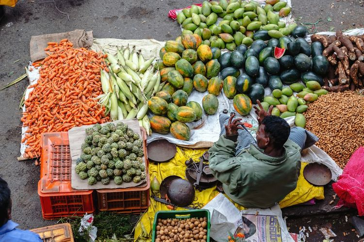 High Angle View Of Vendor Selling Fruits And Vegetables At Market Stall