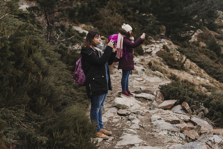 Full length of females photographing while standing on mountain