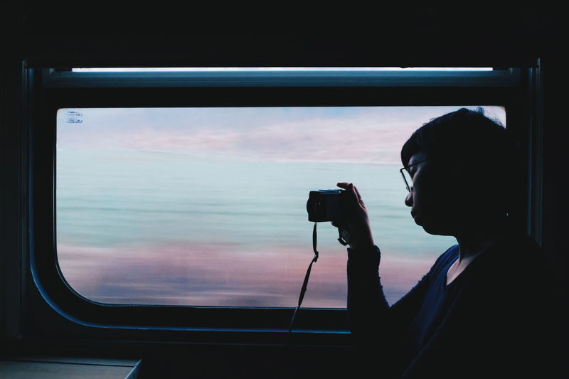 Woman photographing through window in train