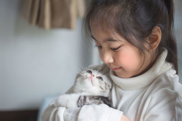 Close-Up Of Girl Holding Kitten