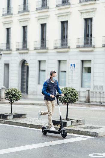 Full length of man riding skateboard on road in city