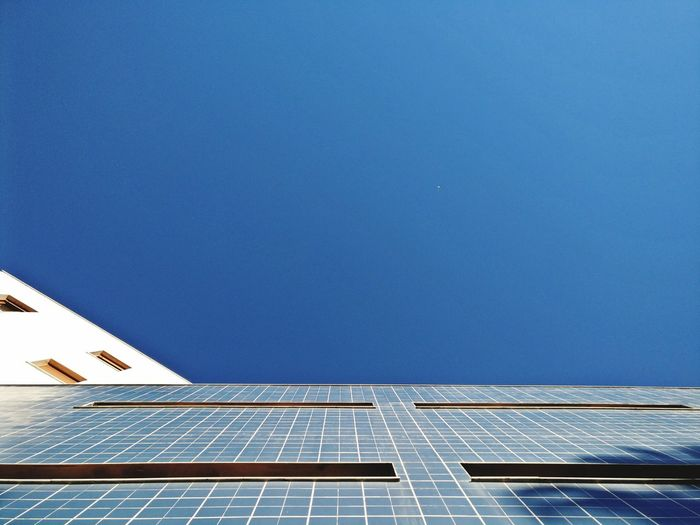 Low angle view of blue sky reflecting on building