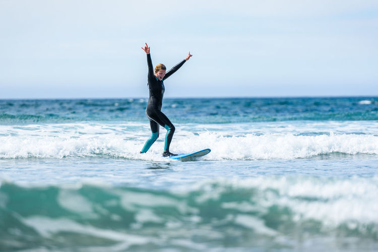 Full length of woman with arm raised surfing in sea against clear sky
