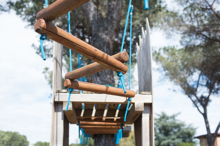 Suspended bridge path in adventure playground Adventure Playground Conquest Day Difficult Game Growth Hanging Out Hindrance No People Ordeal Outdoors Park Path Solution Steps Suspended Bridge Target Tree Wooden