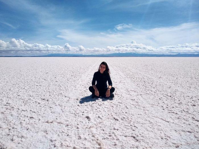 Portrait of smiling woman sitting on salt flat against sky