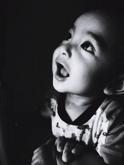 Close-up of baby boy looking up in darkroom
