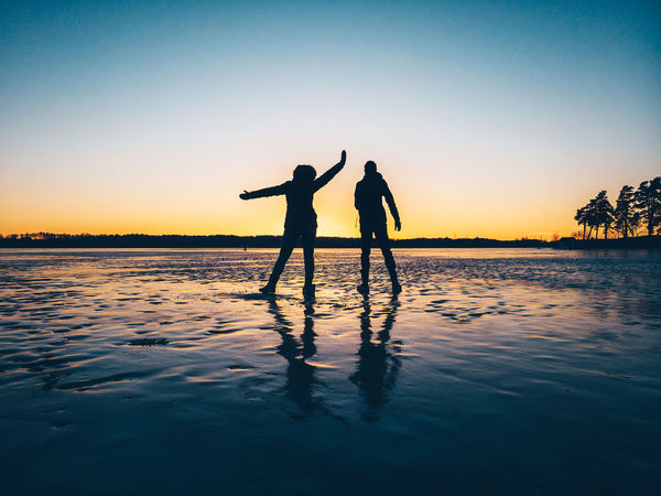 On ice DJI X Eyeem Drone  Silhouettes Beauty In Nature Friendship Human Arm Leisure Activity Lifestyles Mavic Pro Men Nature Orange Color Positive Emotion Real People Scenics - Nature Silhouette Sky Standing Sunset Togetherness Tranquil Scene Tranquility Two People Water Waterfront