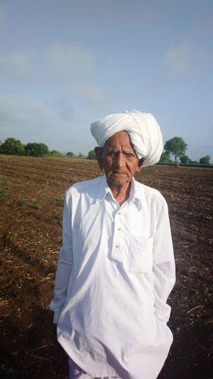 Portrait of senior farmer standing on field against sky