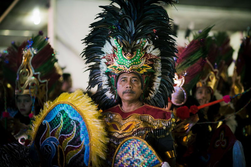 Arts Culture And Entertainment Celebration Chingay Clothing Costume Dancing Feather  Focus On Foreground Front View Headdress Headwear Indoors  Multi Colored One Person Performance Real People Traditional Clothing Traditional Dancing Waist Up