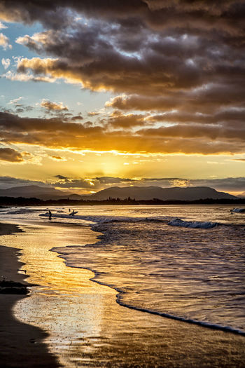 Sunset with surfers Sunset Water Sky Cloud - Sky Sea Scenics - Nature Beauty In Nature Beach Tranquility Land Tranquil Scene Orange Color Nature Idyllic Reflection Non-urban Scene No People Outdoors Remote Surfers Seascape Landscape Scenics Colors Lifestyles