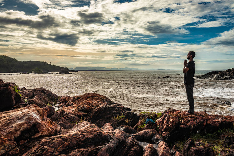 Site view of man standing on rock by sea against sky