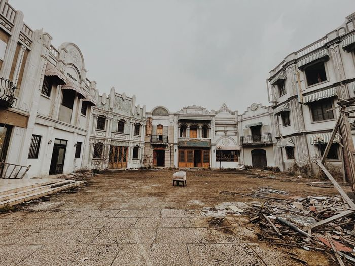 Abandoned buildings against sky in city