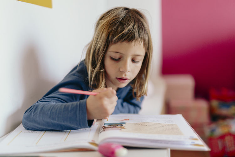 Girl looking at book on table