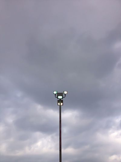 Illuminated floodlight against cloudy sky