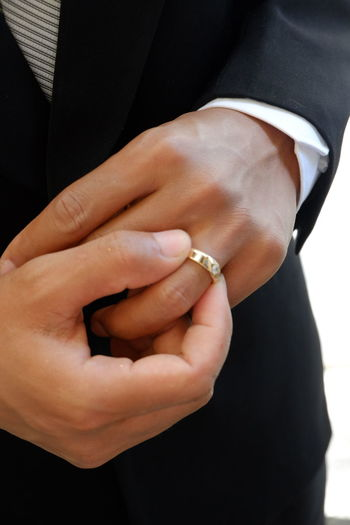Midsection of groom wearing wedding ring