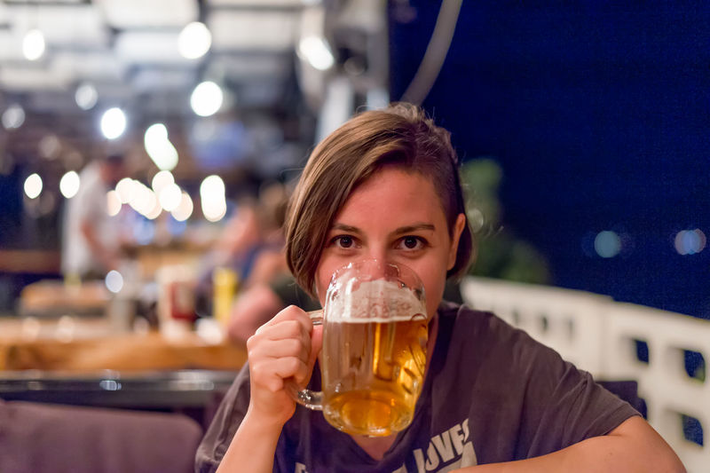 CLOSE-UP OF YOUNG WOMAN DRINKING BEER