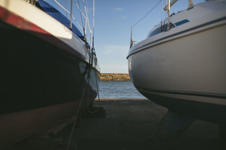 Boats moored in sea against sky