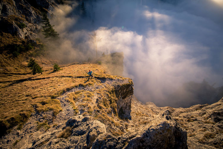 Scenic view of smoke by mountains with woman running on rocks