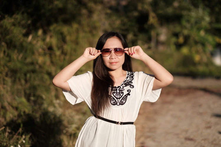 Portrait of smiling young woman wearing sunglasses standing against trees