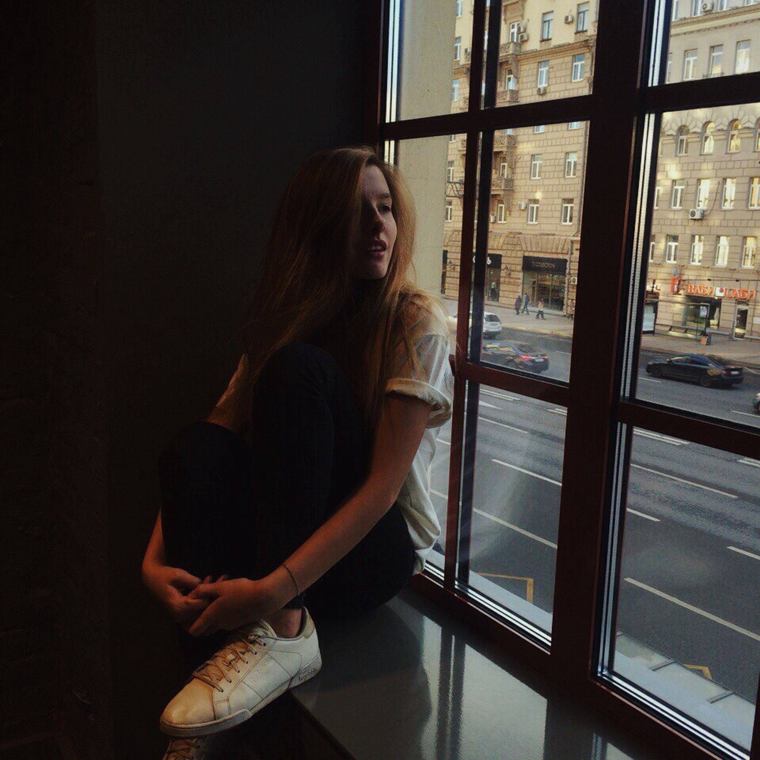 window, indoors, glass - material, casual clothing, transparent, side view, leisure activity, young adult, long hair, person, holding, day, looking, contemplation, profile, traveling