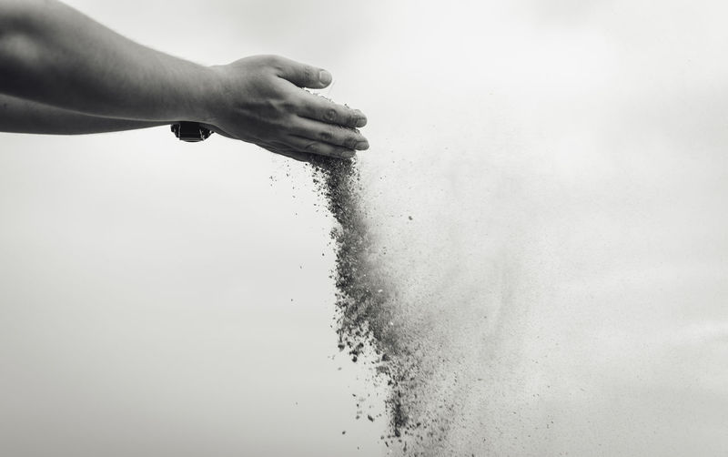 Cropped hand sprinkling sand against sky