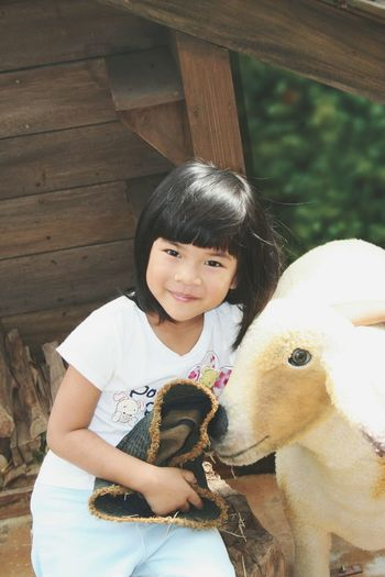 Portrait of cute smiling girl standing by artificial sheep