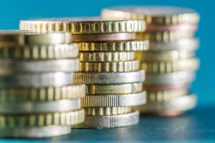 Close-up of stacked coins on table against blue background