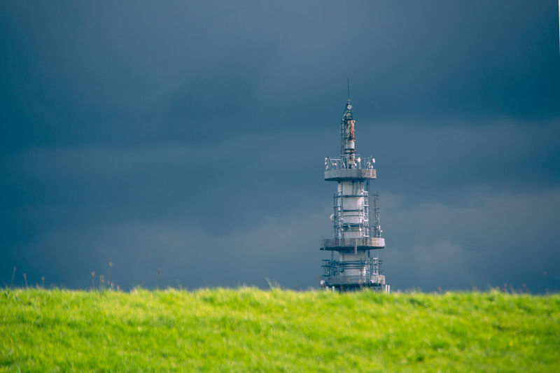 Tower on field by building against sky