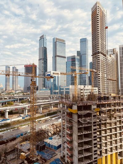 Construction works against the background of moscow skyscrapers and cloudy sky in summer.
