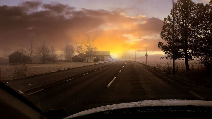 Empty road against cloudy sky at sunset