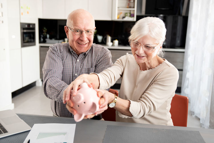 Senior couple holding piggy bank over table