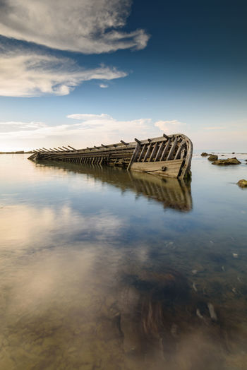 Shipwreck and its reflection in Banten, Indonesia Anyer  Banten INDONESIA Beauty In Nature Blue Sky Cloud - Sky Day Daylight Idyllic Lake Long Exposure Nature No People Non-urban Scene Outdoors Reflection Scenics - Nature Shipwreck Sky Sunset Tranquil Scene Tranquility Water Waterfront