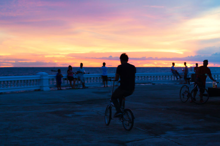 Evening Sky Background Twilight The Great Outdoors - 2018 EyeEm Awards Beach Bicycle Cloud - Sky Group Of People Horizon Over Water Land Leisure Activity Lifestyles Men Nature Orange Color People Real People Riding Sea Silhouette Sky Sport Sunset Transportation Water Friend Seascape Idyllic Dramatic Sky Atmospheric Mood