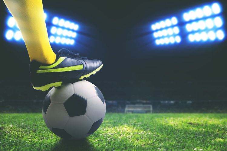 Low section of player kicking soccer ball on field at night
