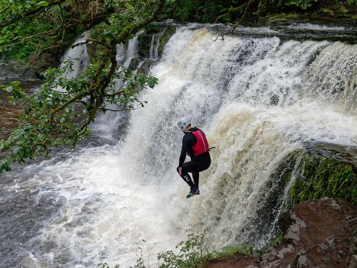 Man surfing in water flowing through rocks
