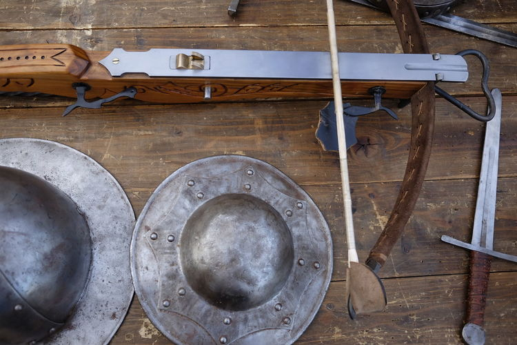High Angle View Of Medieval Weapons On Wooden Table