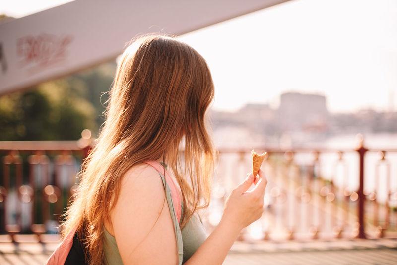 Portrait of woman against railing against sky