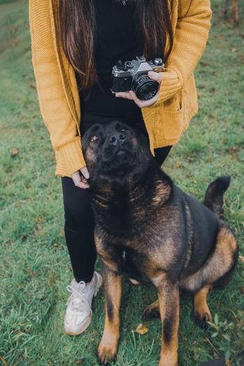 Young woman holding a vintage camera and standing on the grass with a black dog