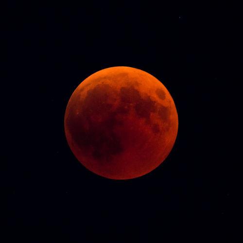Orange moon against sky at night