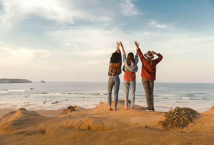 Rear view of friends standing with arms raised at beach