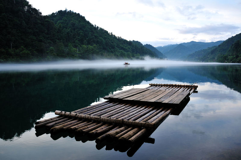 Wooden raft on lake amidst mountains against sky