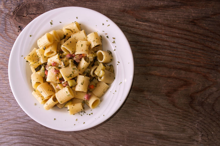Rigatoni pasta with bacon and zucchini Bowl Close-up Directly Above Food Food And Drink Freshness Healthy Eating High Angle View Indoors  Italian Food Macaroni No People Pasta Plate Ready-to-eat Serving Size Still Life Table Temptation Wellbeing Wood - Material