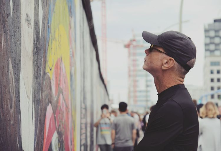 Man looking at graffiti on wall while standing in city